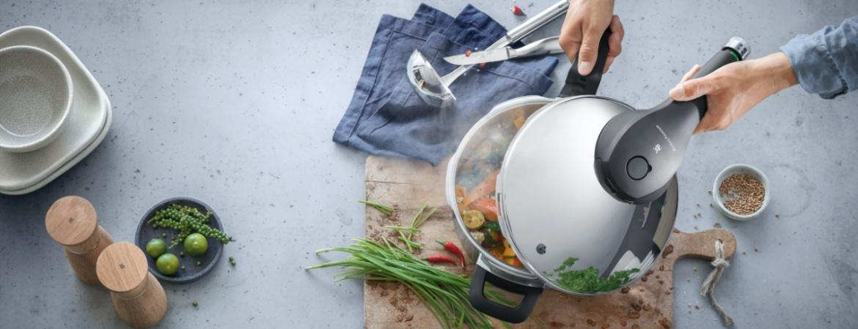 WMF Schnellkochtopf steht in einer Küche, ist umgeben von Küchenutensilien und Kochzutaten und wird gerade geöffnet