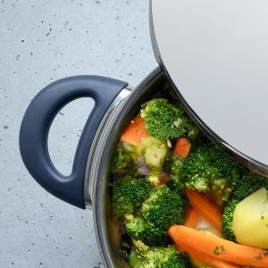 Der Deckel des WMF Schnellkochtopfes ist halb geöffnet, darin befindet sich Gemüse