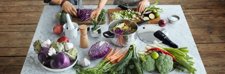 Der WMF Schnellkochtopf steht auf einem Marmortisch und ist von Gemüse umgeben, das von zwei Personen zubereitet wird