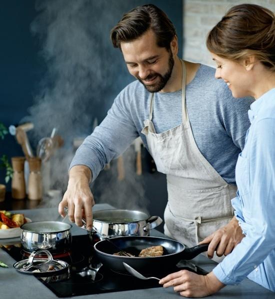 eine junge frau und ein junger mann kochen gemeinsam an einem herd mit topfen und pfannen von wmf