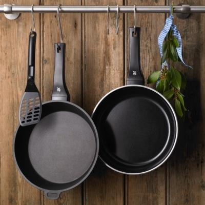 wmf pfannen hängen an einem küchenhaken vor einer holzwand