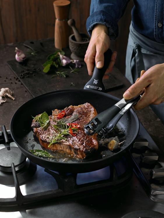 ein frisch zubereitetes steak in einer neu gekauften wmf pfanne auf einem gasherd