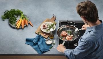 eine wmf pfanne auf einem herd mit einem kochenden mann und verschiedenen lebensmitteln zur zubereitung