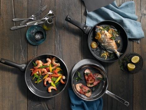 wmf pfannen von oben auf einem holztisch, in denen verschiedene speisen zubereitet werden